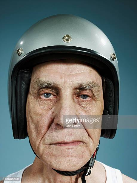 a headshot of a frowning senior man wearing a crash helmet - crash helmet stock pictures, royalty-free photos & images