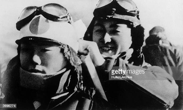 Headshot of a Japanese 'kamikaze' pilot smiling while helping another pilot with his gear during World War II. They are wearing white scarves, a...