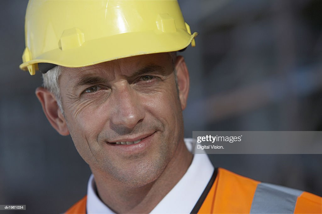 Headshot of a Man Wearing a Hard Hat and a Fluorescent Jacket : Stock Photo