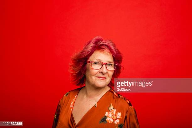 headshot of a senior woman on a red background - bright colour stock pictures, royalty-free photos & images