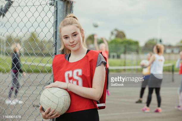 headshot of a teenage girl holding a netball - girls stock pictures, royalty-free photos & images