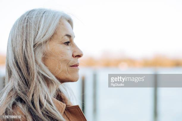 headshot of a thoughtful mature woman looking at the distance - distant stock pictures, royalty-free photos & images