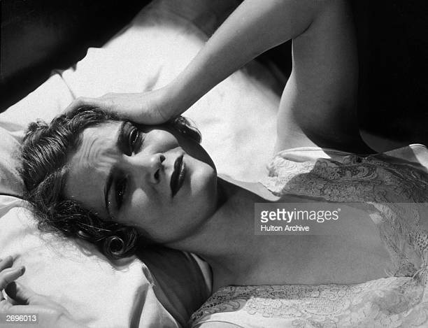 Headshot of a worried looking sick woman laying in bed with her head on a pillow holding a hand up to her head 1930s