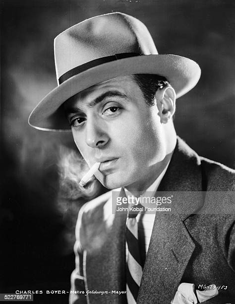 Headshot of actor Charles Boyer smoking a cigarette and wearing a hat for MGM Studios 1931