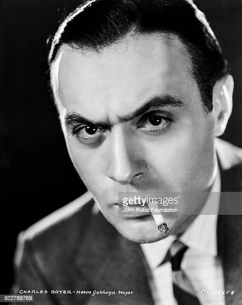 Headshot of actor Charles Boyer smoking a cigarette for MGM Studios 1931