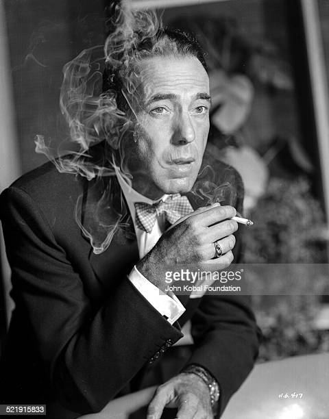 Headshot of actor Humphrey Bogart , wearing a bow tie and smoking a cigarette, for Warner Bros Studios, 1950.