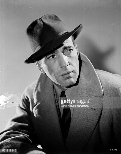 Headshot of actor Humphrey Bogart wearing a hat and an overcoat, for Warner Bros Studios, 1939.