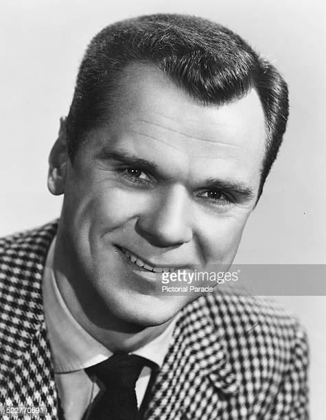 Headshot of actor Jackie Cooper wearing a check jacket and tie circa 1960