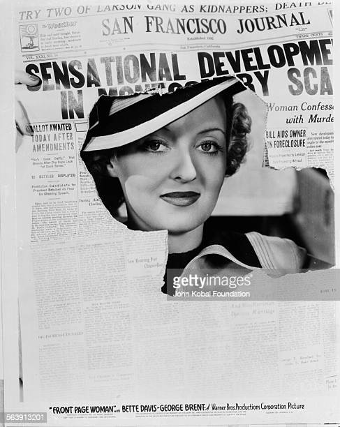Headshot of actress Bette Davis peering through a hole in a newspaper as she appears in the film 'Front Page Woman' for Warner Bros Studios 1935
