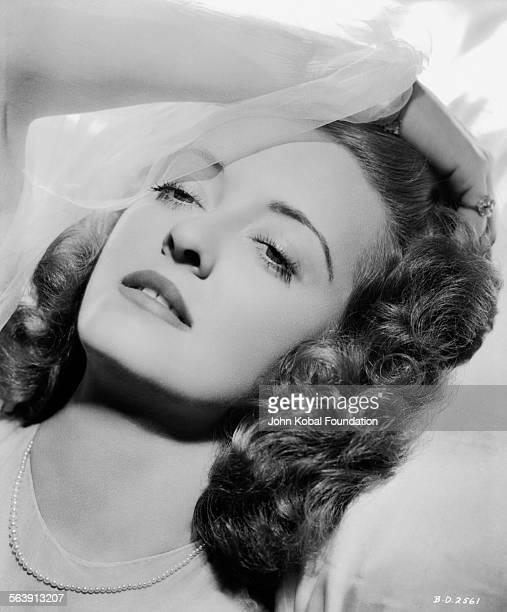 Headshot of actress Bette Davis running her hand through her hair for Warner Bros Studios 1939
