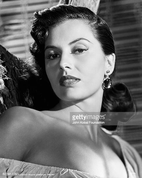 Headshot of actress Cyd Charisse wearing an off the shoulder blouse for MGM Studios August 14th 1952