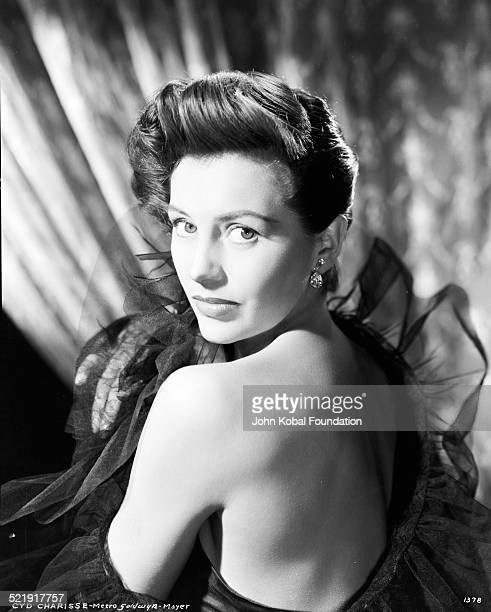 Headshot of actress Cyd Charisse with her bare back facing the camera for MGM Studios August 14th 1952