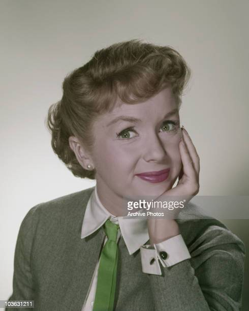 Headshot of actress Debbie Reynolds pictured wearing a green jacket and green tie while resting her head on her left hand circa 1970