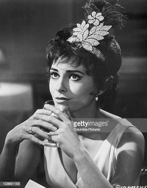 Headshot of actress Elizabeth Ashley pictured wearing a feather headdress, and holding a glass of brandy to her lips, in a scene from the film, 'Ship...
