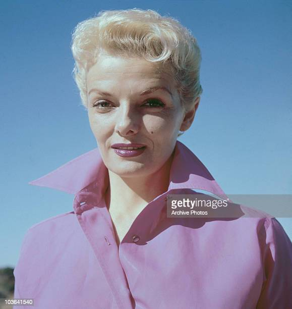 Headshot of actress Jane Russell pictured wearing a widecollared pink shirt USA circa 1960 A blonde Russell is also wearing lipstick which matches...