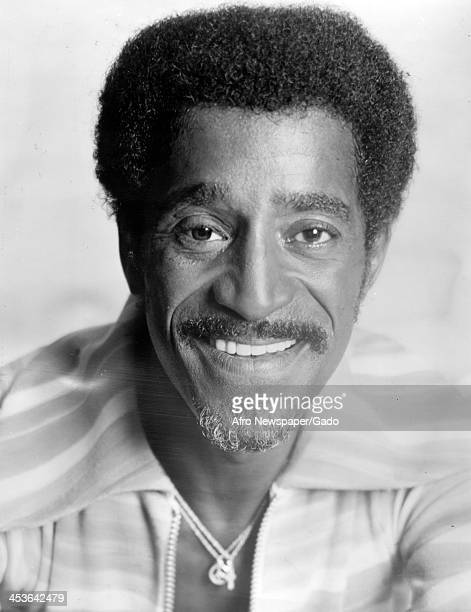 Headshot of African American entertainer Sammy Davis Junior with a peace sign necklace 1970