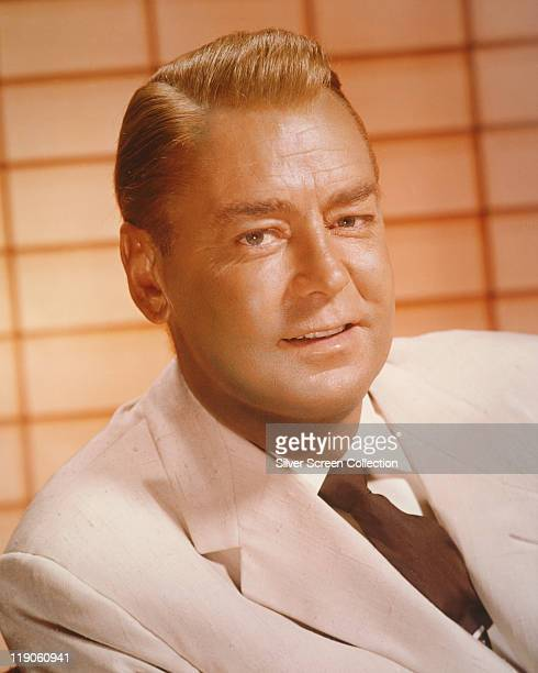 Headshot of Alan Ladd , US actor, poses for a studio portrait wearing a light-coloured jacket, white shirt and dark tie, USA, circa 1957.