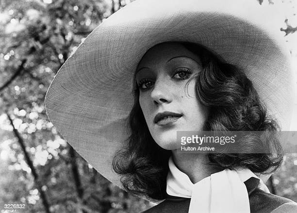 Headshot of American actor Marisa Berenson wearing a wide-brimmed hat and silk scarf in a low-angle promotional headshot for Bob Fosse's film,...