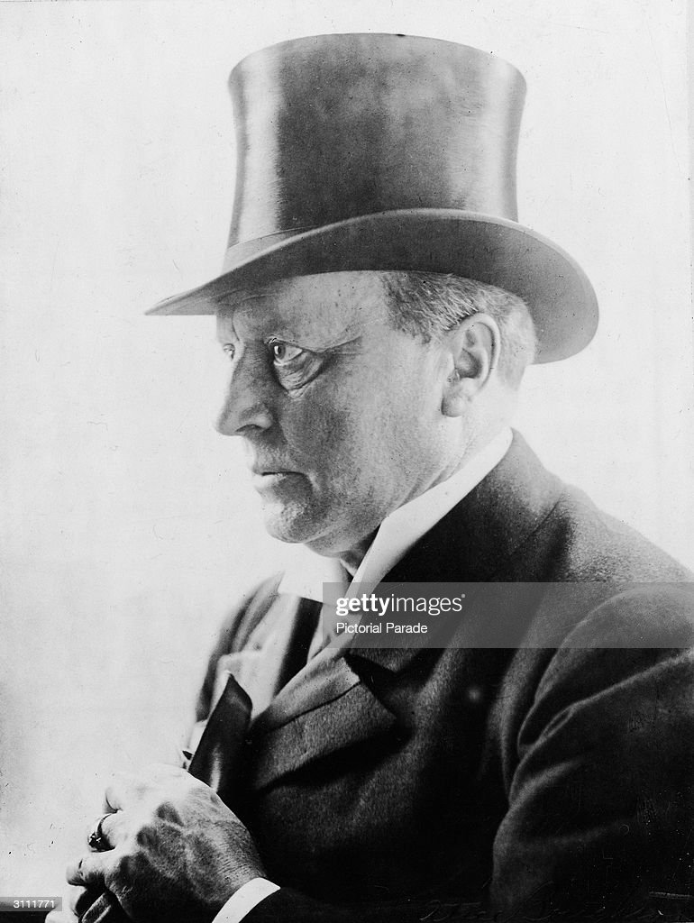 Headshot of American author Henry James (1843 - 1916) wearing a top hat, 1900s.