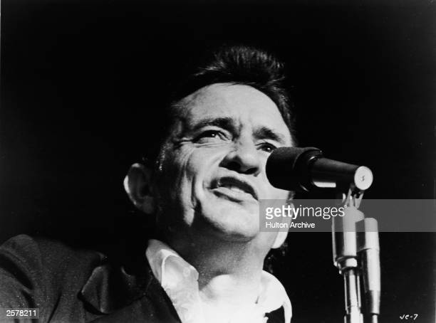Headshot of American country singer Johnny Cash singing on stage in a still from the film 'Johnny Cash The Man His World His Music' directed by...