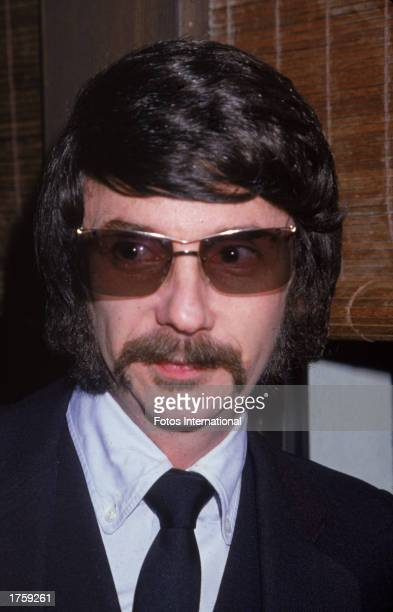 Headshot of American music producer Phil Spector wearing sunglasses indoors, 1980.