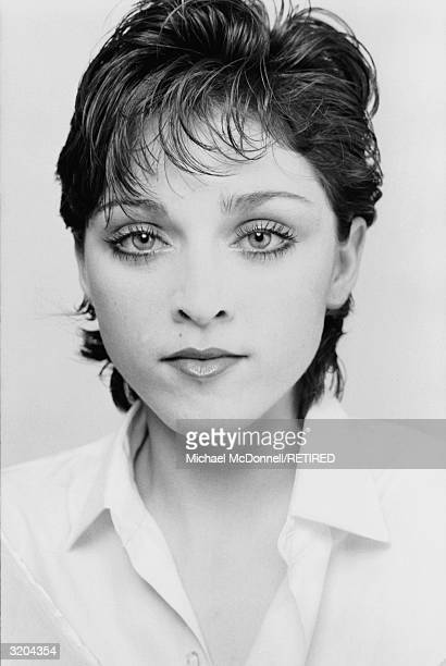 Headshot of American pop singer Madonna wearing an open-necked blouse with short, dark hair, New York City, Spring 1979.