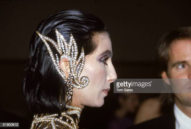 Headshot of American popular singer and actress Cher with an extremely elaborate piece of ear jewelry as she attends the opening of an exhibition at...