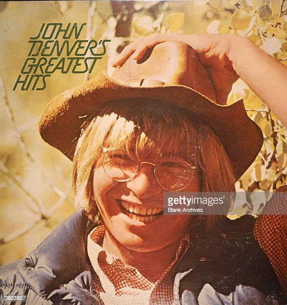 Headshot of American singer musician and actor John Denver laughing while holding his hat on the cover of his record album 'John Denver's Greatest...