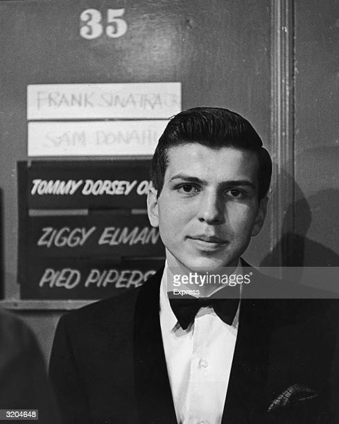 Headshot of American vocalist Frank Sinatra Jr wearing a tuxedo while standing in front of the dressing room door he shared with other performers at...