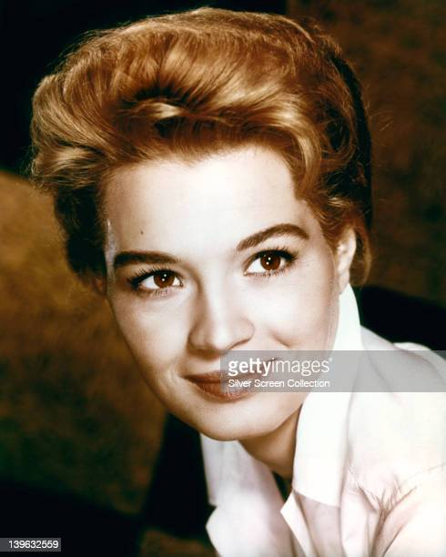 Headshot of Angie Dickinson US actress wearing a white blouse in a studio portrait against a dark background circa 1960