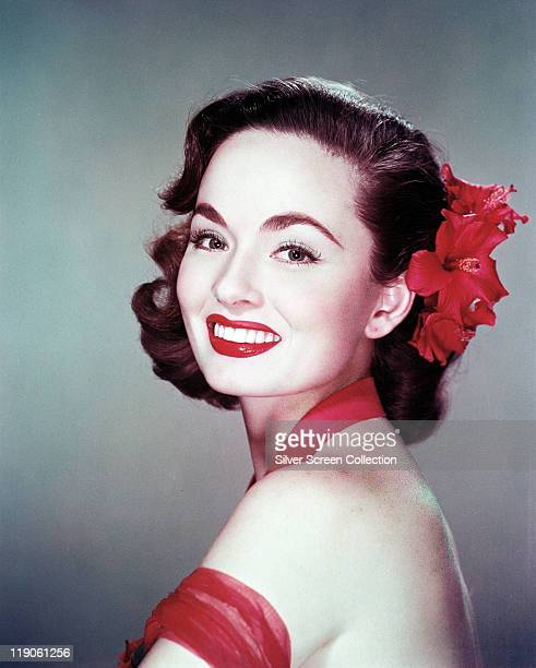 Headshot of Ann Blyth US actress with a red flower in her hair in a studio portrait circa 1950