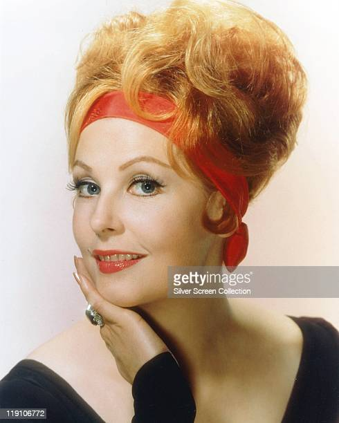 Headshot of Arlene Dahl US actress wearing a red headband with her chin resting on her hand in a studio portrait circa 1970