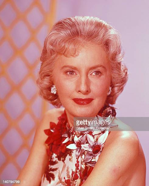 Headshot of Barbara Stanwyck US actress wearing a halterneck top with floral motifs in a studio portrait against a pink background circa 1960