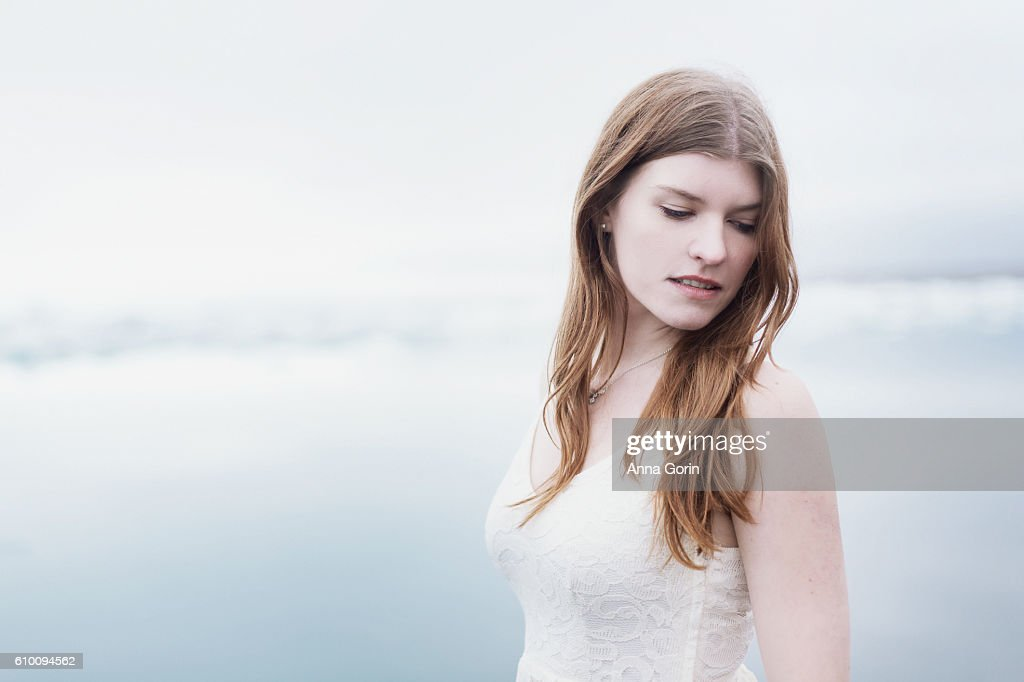 Headshot of beautiful young woman in sleeveless white lace dress, looking down, bright outdoor background : Stock Photo