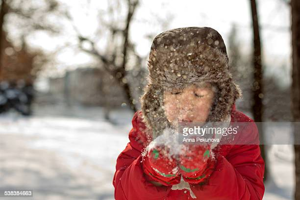 Headshot of boy blowing out snow