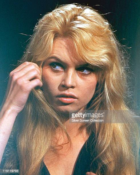 Headshot of Brigitte Bardot French actress model and singer playing with her hair while looking nervous in a studio portrait 1965