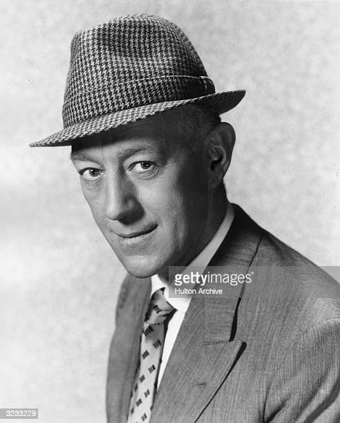 Headshot of British actor Alec Guinness wearing a houndstooth hat in a promotional portrait for director Mervyn Leroy's film 'A Majority of One'