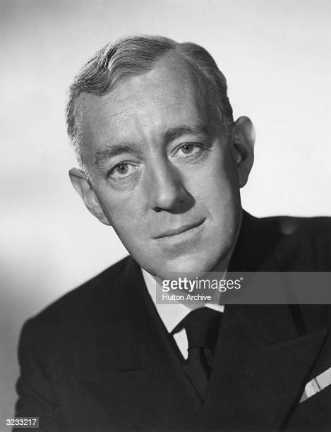 Headshot of British actor Alec Guinness wearing a sea captain's uniform in a promotional portrait for director Charles Frend's film 'Barnacle Bill'...