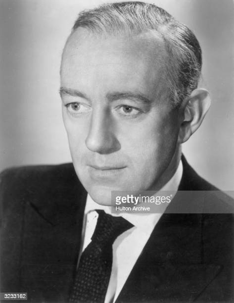 Headshot of British actor Alec Guinness wearing a suit and tie in a promotional portrait for director Ronald Neame's film 'The Horse's Mouth'
