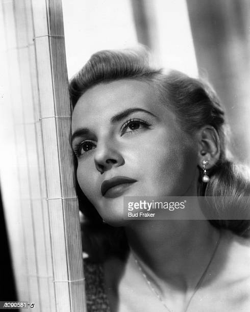 A headshot of British actor Elaine Aiken leaning against a doorframe