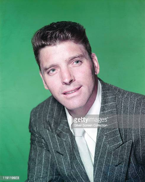 Headshot of Burt Lancaster US actor wearing a pinstriped jacket and white shirt in a studio portrait against a green background circa 1950