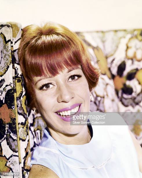 Headshot of Carol Burnett US actress singer and dancer wearing pink lipstick smiling while resting her head against a patterned cushion circa 1970