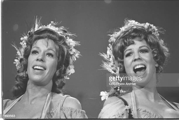 Headshot of comic actors Carol Burnett and Vicki Lawrence singing wearing flowers in their hair in a musical skit from 'The Carol Burnett Show'...
