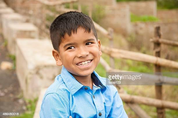 Headshot of cute Latin or Asian boy at park, street.