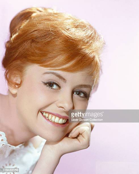 Headshot of Deborah Walley US actress smiling with her chin reasting on her hand in a studio portrait against a white background circa 1960