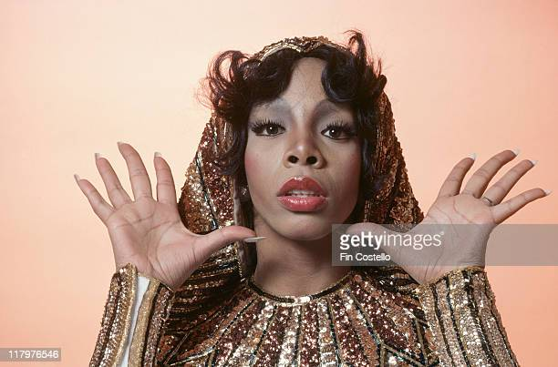 Headshot of Donna Summer US singersongwriter posing in a studio portrait with her hands raised openpalmed either side of her head wearing...