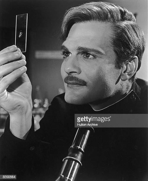 Headshot of Egyptian actor Omar Sharif examing a slide sample in a still from British director David Lean's film 'Doctor Zhivago'