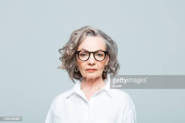 disparo a la cabeza de la mujer de negocios de edad avanzada con camisa blanca - camisa blanca fotografías e imágenes de stock