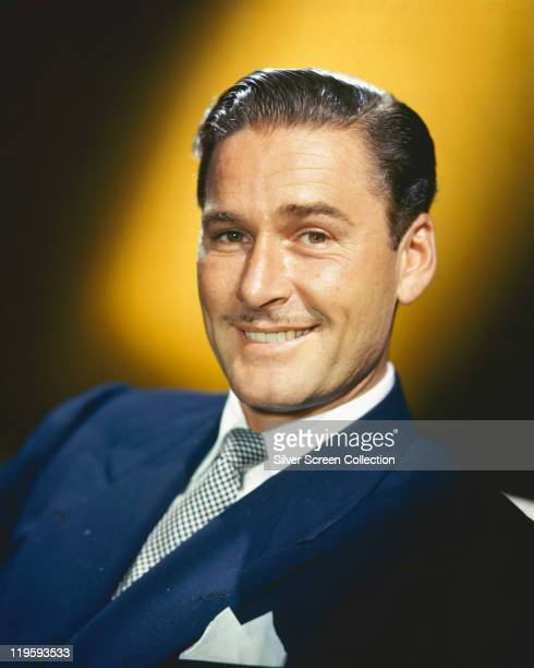 Headshot of Errol Flynn Australian actor wearing a blue jacket white shirt and blueandwhite check tie in a studio portrait with a yellow background...