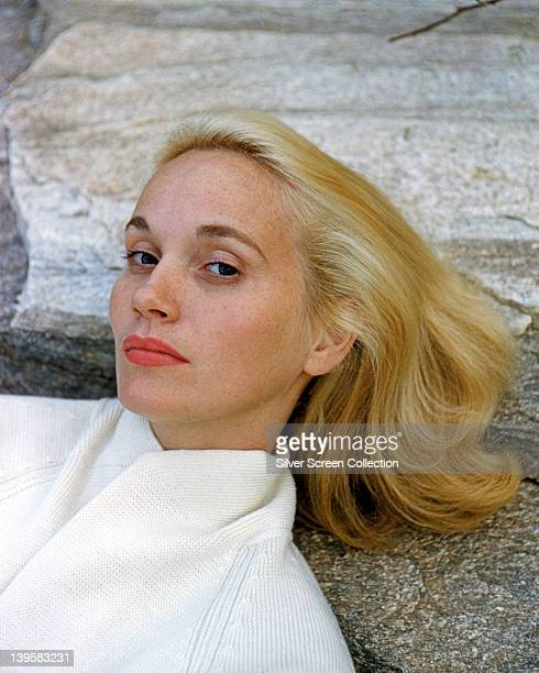 Headshot of Eva Marie Saint US actress wearing a white knitted cardigan posing against a rock circa 1960
